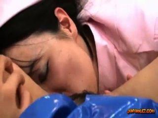 警察制服的亞裔女孩舔了與玩具由在床上的一位護士在