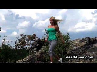 运动的金发女郎在岩石上下了一个小便