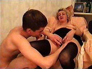 成熟的女人和一個年輕人採取一些酒
