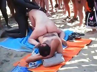 偷窺海灘群體性在大家面前的海灘上。