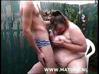 肥胖的母狗在花園裡吸吮公雞,讓她的奶子奶油