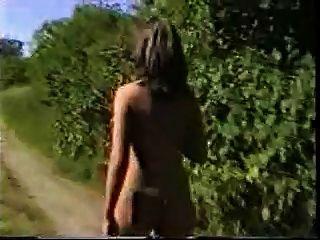 熱的婦女裸體在鐵路附近走