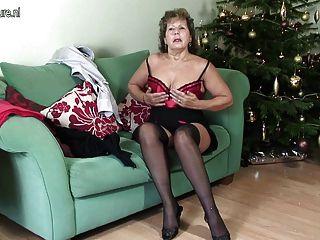 成熟的英國家庭主婦在她的長沙發淘氣