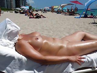 在裸體海灘的完善的胸部