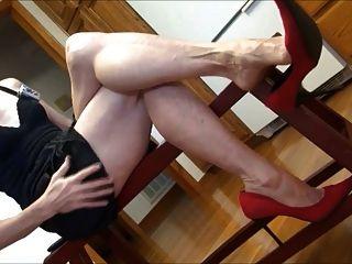 成熟的腳和紅色的高跟鞋搖晃
