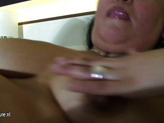 成熟的蕩婦媽媽玩在她的床上與一個假陽具