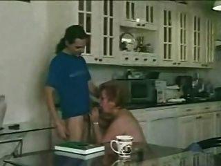 毛茸茸的奶奶滿足年輕的男孩在廚房裡