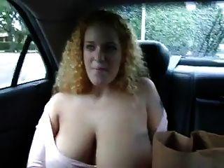 豐滿的紅發顯示她的胸部在車後座