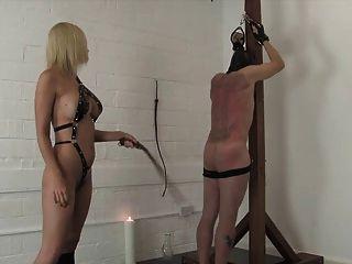 捲曲的金發女主人鞭打和折磨她的奴隸