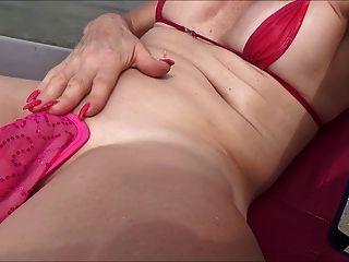 在海灘的sissy盪槳與c串和玫瑰花蕾