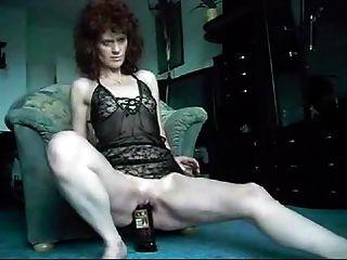 成熟夫人吞下威士忌酒瓶