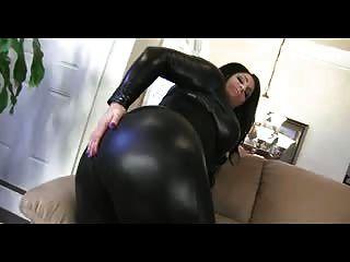 彎曲的淺黑膚色的男人炫耀皮革catsuit的巨大的屁股