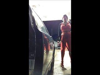 在一件紅色禮服的加油站在一個大風天