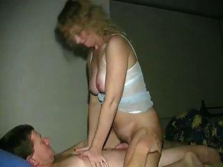 有大山雀的怪异的金发女郎骑着她的男朋友