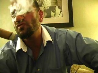 热的肌肉大块吸烟雪茄和起重机