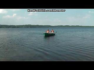 金色的女孩在湖上三个人的船上,
