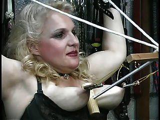 丰满的金发女郎被她的山雀虐待,在地下城玩绳