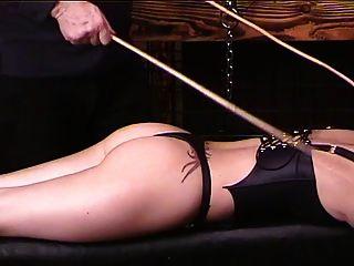 黑发在皮革蓬松的谎言躺在长凳上,花了两个手杖给她