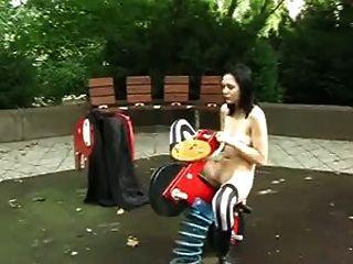 哥特女孩裸露在操场玩具上