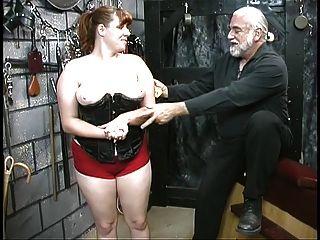 年轻的bdsm奴隶女孩黑发在紧身胸衣被打屁股在地下室