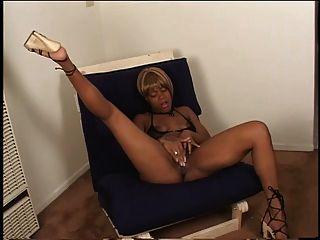 高跟鞋的性感乌木指着她多汁的猫在椅子上
