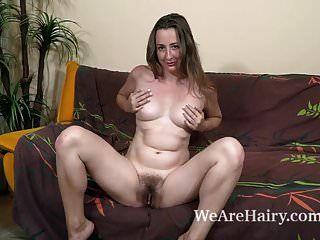 露西亚西伯利亚在她的棕色沙发上脱光衣服